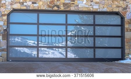 Panorama Garage Door With Glass Panes Reflecting A Snowy Hill Landscape Under Blue Sky