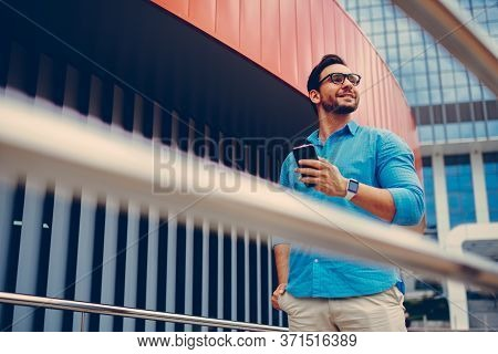 Handsome Tourist Chatting With Best Friend Via Phone While Strolling In Downtown