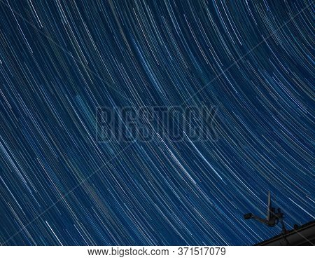 satellite antenna in front of night sky with star trails