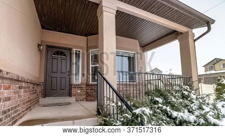 Panorama Home With Bay Window Sidelight And Glass Paned Wooden Door Against Cloudy Sky
