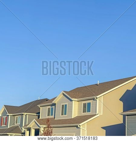 Square Frame Homes With Horizontal Wall Sidings And Front Gable Roofs Againts Clear Blue Sky