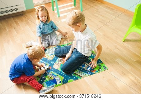 Children Playing With Cars On A Road Themed Carpet. Kids At Home Or Daycare.