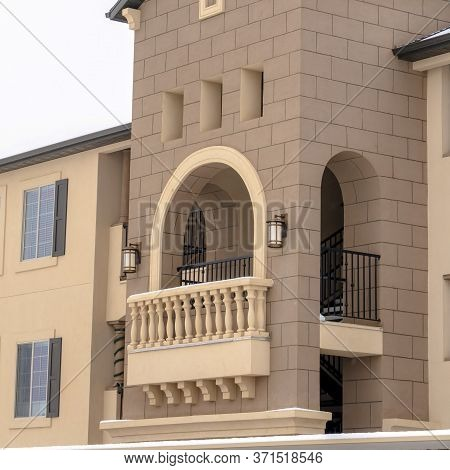 Square Apartment With Snowy Front Gable Roof And Balustrade On The Arched Balcony