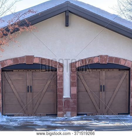 Square Crop Facade Of A Residential Garage With Gable Roof And Two Hinged Wooden Doors