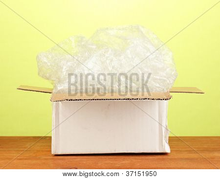 Opened parcel on green background close-up