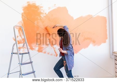 Happy Young Woman Painting Interior Wall With Paint Roller In New House. A Woman With Roller Applyin