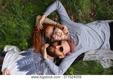 Closeup Portrait Of A Beautiful Couple, Seated Down On A Green Grass, Seated Down With Turned Heads