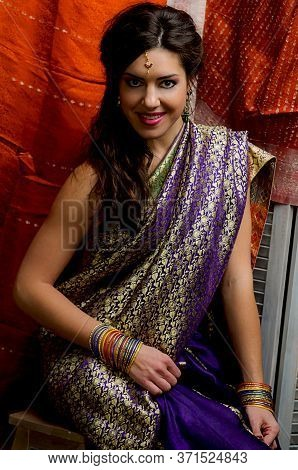 The Young Dark-haired Woman In The Rich Indian Saris And Colorful Bracelets Smiling Sitting On A Bac