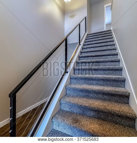 Square Frame Indoor Stairs Of Home With Metal Handrail And Gray Carpet On The Treads