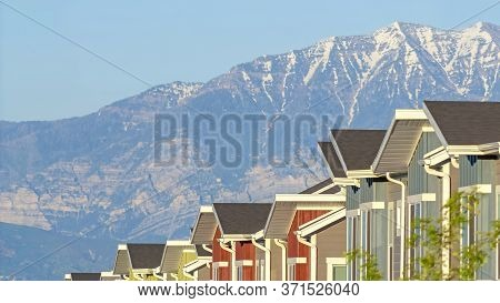 Panorama Frame Snowy Mountain And Blue Lake View Behind Townhouses With Colorful Exterior Walls