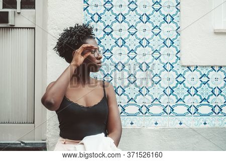 Dazzling Young African Female Is Adjusting Eyeglasses While Standing In Front Of Traditional Azulejo