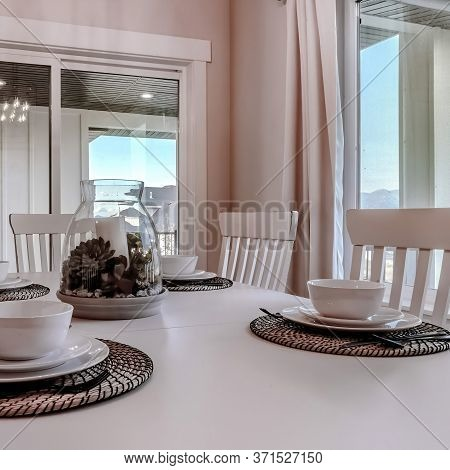 Square Frame Dining Table With Chairs And Tableware Arranged Around A Decorative Centerpiece