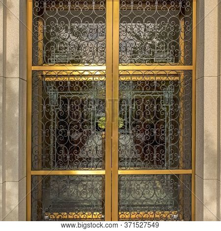 Square Crop Decorative Wrought Iron Door With Gold Frames In Front Of Glass Door Of Building