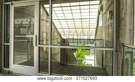 Panorama Glass Door And Wall With View Of Slanted Frosted Roof Over Stairway Of Building