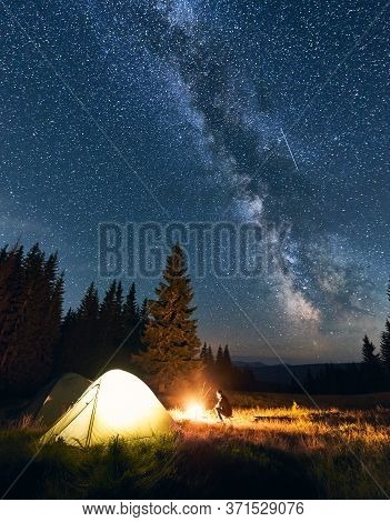 Lonely Guy Sitting Near Campfire In Campsite Under Starry Sky In The Mountains. Night Sky Is Strewn