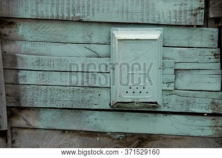 Old Painted Mail Box On A Wooden Green Wall.
