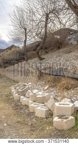 Vertical Crop Conctere Blocks Of A Collapsed Low Retaining Wall Lining A Slope And Dirt Road