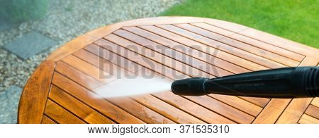Cleaning Garden Table With A Power Washer - High Water Pressure Cleaner On Wooden Exotic Table Surfa