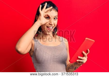 Young woman holding touchpad tablet smiling happy doing ok sign with hand on eye looking through fingers