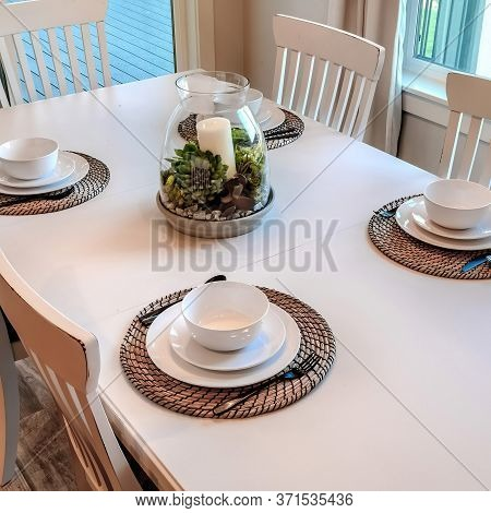 Square Frame Dinner Table Setting With Tableware On Placemats Arranged Around A Centerpiece
