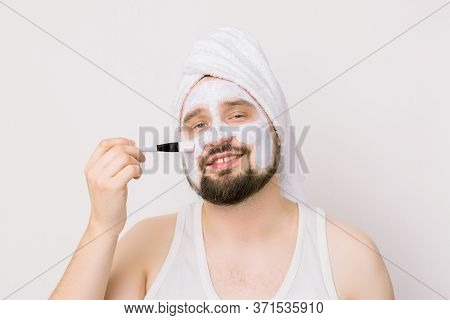 Portrait Of Smiling Handsome Bearded Man, Applying Cleansing Face Mask To His Face Using A Cosmetic