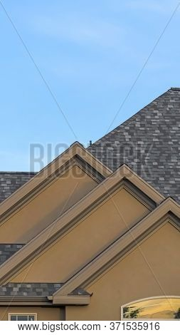Vertical Frame Home Exterior With Front Gable Roof And Transom Window Against Blue Sky