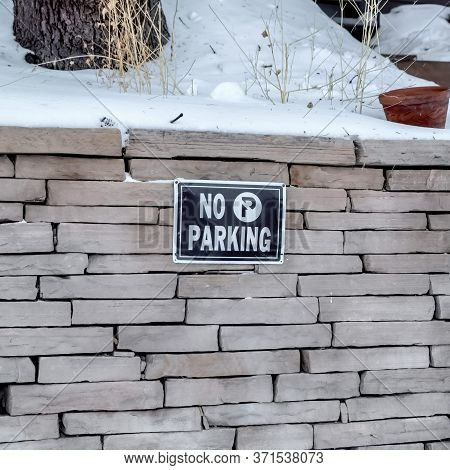 Square Frame No Parking Sign On A Stone Brick Retaining Wall Topped With Snow In Winter