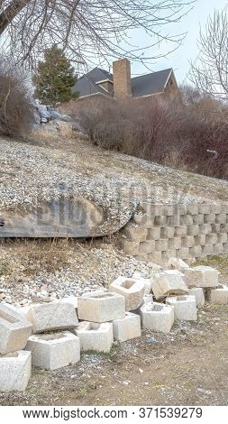 Vertical Stone Blocks Of Collapsed Retaining Wall Holding The Soil Of A Slope With Houses