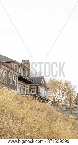 Vertical Grassy Hill With Huge Houses And Retaining Wall Against Cloudy Sky Background