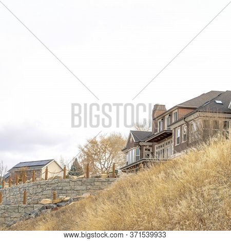 Square Grassy Hill With Huge Houses And Retaining Wall Against Cloudy Sky Background