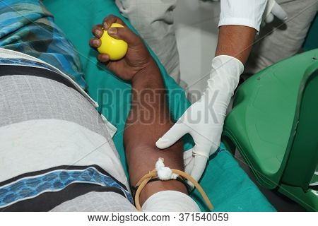 Blood Donor At Donation With A Bouncy Ball Holding In Hand. Original Image For World Blood Donor Day