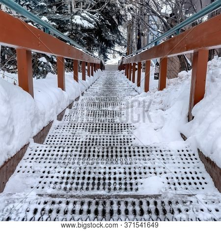 Square Crop Grate Tread Stairs With Wood And Metal Hansrail Against Snowy Hill In Winter