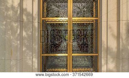 Panorama Decorative Wrought Iron Door With Gold Frames In Front Of Glass Door Of Building