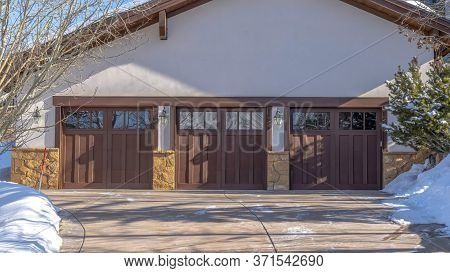 Panorama Driveway Leading To Three Wooden Garage Doors With Glass Panes In Park City Utah