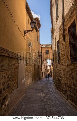 TOLEDO, SPAIN - April 26, 2019: People walking in Toledo Angel street arch, Castile La Mancha. Spain