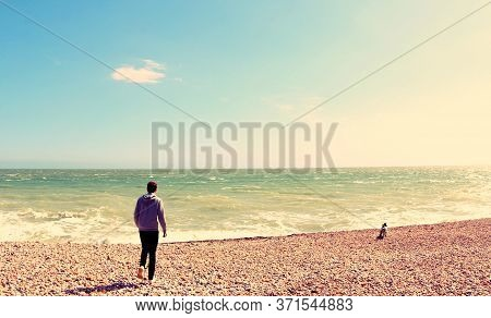 Man Taking Dog For A Walk On The Shoreline