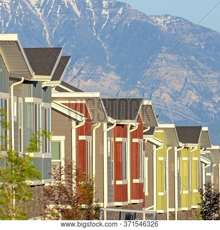 Square Crop Snowy Mountain And Blue Lake View Behind Townhouses With Colorful Exterior Walls