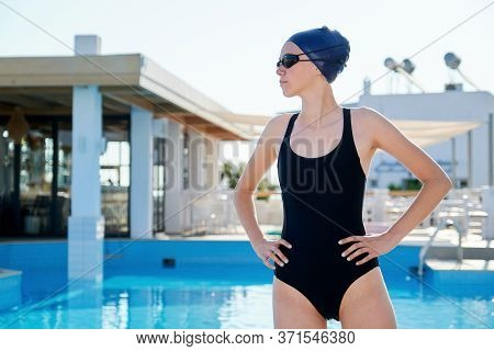 Portrait Of Young Woman Swimmer Wearing Swim Goggles Swimming Cap, Outdoor Swimming Pool Background.