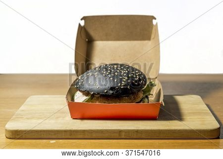Black Burger Lies On A Cutting Board On A Wooden Table