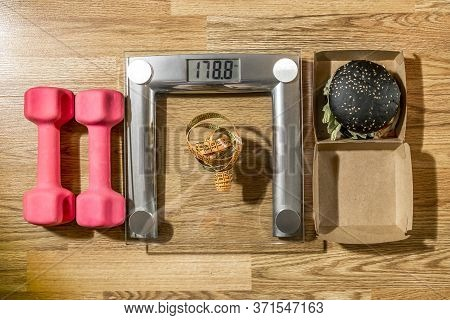 Black Burger Lies Next To The Scales, Measuring Tape And Dumbbells.