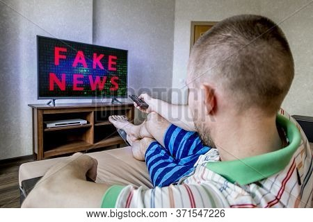 A Man Is Sitting On A Sofa And Watching Tv With Fake News On The Screen