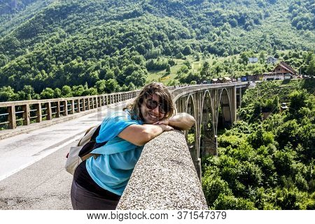 The Tara River Canyon.montenegro.june 04, 2015. A Tourist Girl Poses On The Djurdjevic Bridge Over T