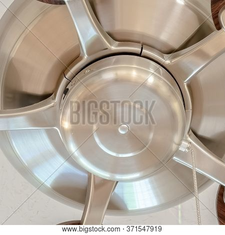 Square Ceiling Fan With Wooden Blades And Lights Mounted On The Ceiling Of A Home