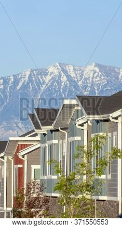 Vertical Townhouses Exterior With Scenic Lake And Snowy Steep Mountain Background