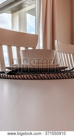Vertical Tableware And Utensils On Woven Placemat At The Dining Table With Chairs