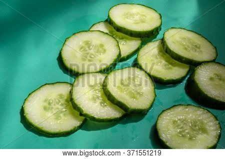 Sliced Flavorful Cucumber Sliced Across In The Sun. Fresh Cucumber Cut Into Pieces On A Turquoise Ba