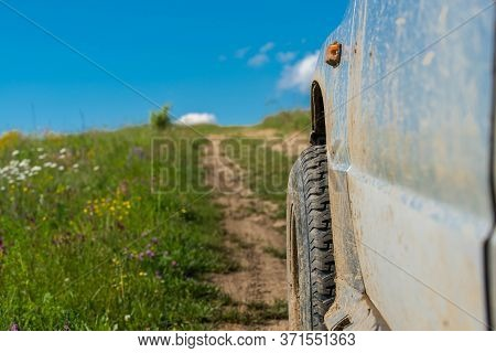 Off Road Tire In Focus, Parking Dirty Off Road Vehicle On Dirt Road At Summertime.