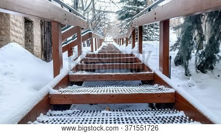 Panorama Crop Focus On Grate Metal Treads Of Outdoor Stairs Against Snowy Hill In Winter