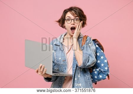 Shocked Young Woman Student In Denim Clothes Glasses Backpack Isolated On Pastel Pink Background. Ed