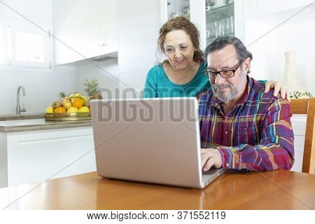 A Couple Of Smiling Seniors Using A Laptop Computer At Home.  Adaptation To The Technology Of Older